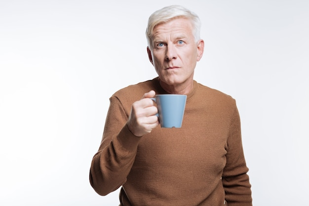 Плохой кофе. седовласый старший мужчина держит синюю чашку кофе и хмурится, недовольный плохим вкусом кофе