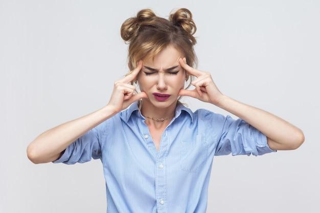 悪い感情と感情の概念。頭の指に触れて片頭痛を持っているブロンドの女性。スタジオショット、灰色の背景