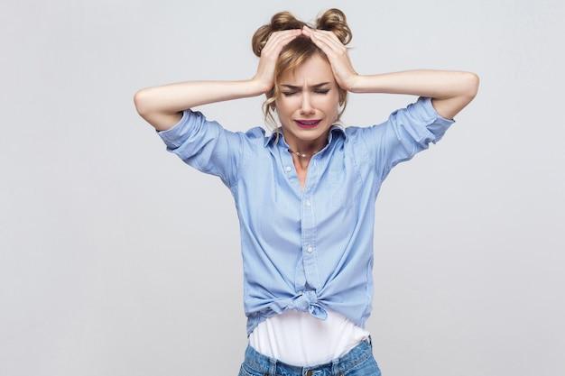 悪い感情と感情の概念。頭痛。頭に触れて片頭痛を持っているブロンドの女性。スタジオショット
