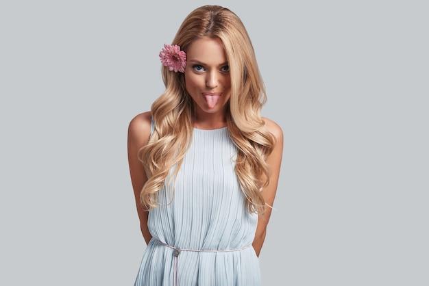 Плохая девочка. игривая молодая женщина с цветком в волосах, глядя в камеру и высунув язык, стоя на сером фоне