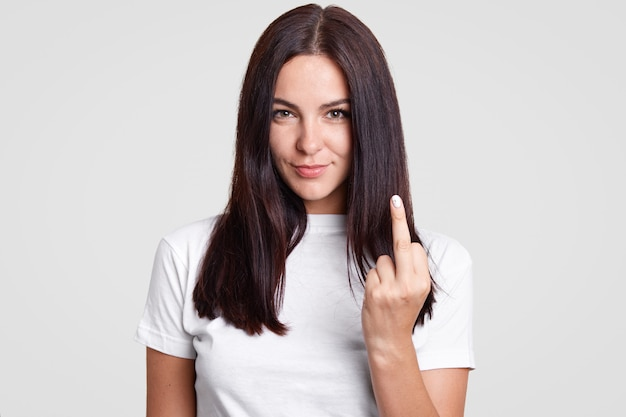 Bad girl with straight dark hair shows fuck sign, looks mysteriously at camera, wears casual t shirt