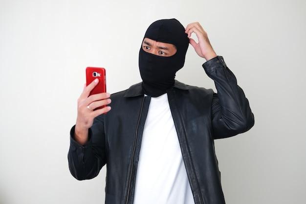Плохой парень в балаклаве показывает смущенный жест, глядя на мобильный телефон