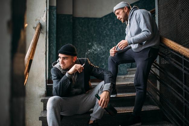 Плохие парни ждут жертву на лестнице и курят. уличный грабитель, криминальная опасность. понятие преступления