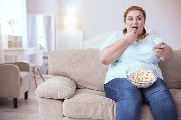 Плохие привычки. мечтательная рыжая женщина сидит на диване и ест попкорн во время просмотра телевизора