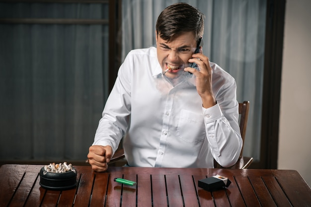 Bad habits. portrait of a guy in a rage, posing while sitting at a table
