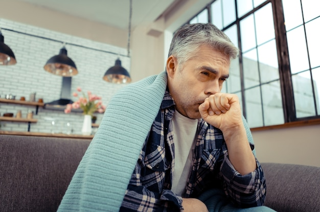 体調不良。強い咳に苦しんでいる間、病気休暇中の元気のない不幸な男