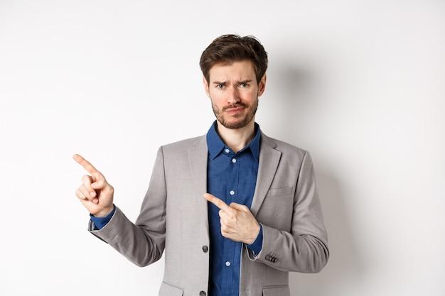 Плохая идея. недовольный скептически настроенный парень в деловом костюме ухмыляется и хмурится, указывая пальцами влево на неприятные новости, нерешительно смотрит в камеру, белый фон.