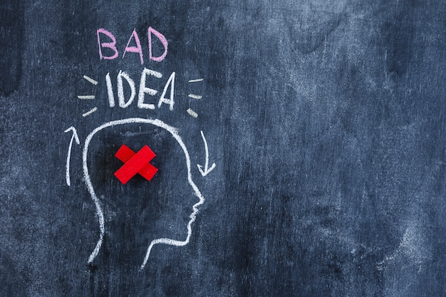 Bad idea text over the head with red crossed in the head drawn on chalkboard