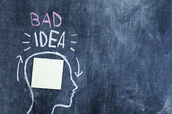 Bad idea text over the head with blank sticky note in head drawn on chalkboard