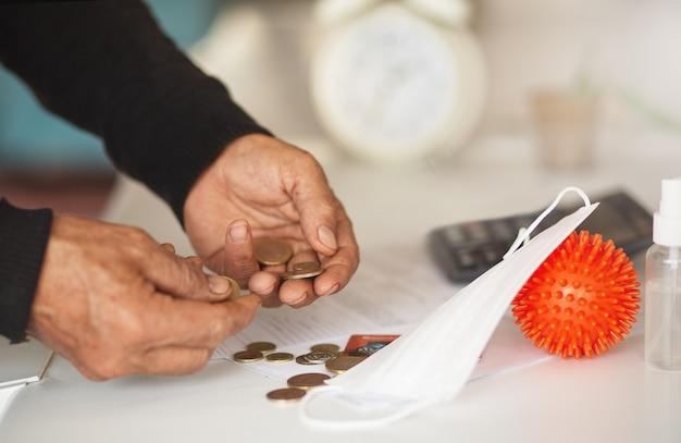바이러스 개념으로 인한 나쁜 투자 또는 경제 위기. 수석 남자는 동전을 세는 손, 바이러스 위기 공격. 코로나 19