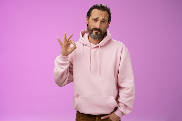 Not bad may better. portrait handsome mature bearded father wearing trendy hoodie frowning awkward show okay ok normal gesture unimpressed but agree, standing purple background doubtful unsure.