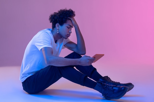 Bad mood. curly-haired young guy holding a tablet and looking frustrated