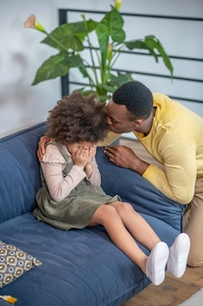 Bad mood. darkskinned little girl covering face with hands sitting on sofa at home and worried young dad hugging shoulders