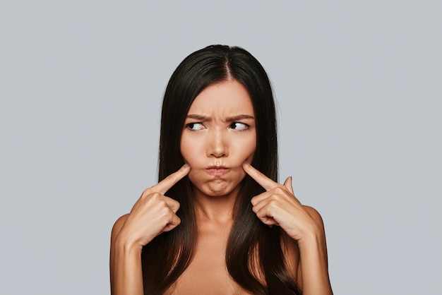 In a bad mood. displeased young asian woman making a face while standing against grey background