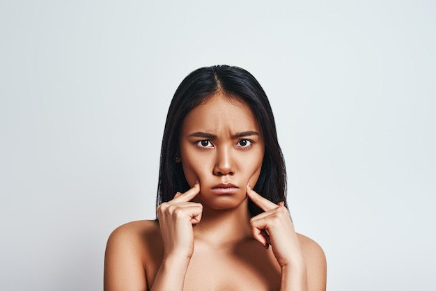 In a bad mood upset young asian woman making a face and feeling sad while