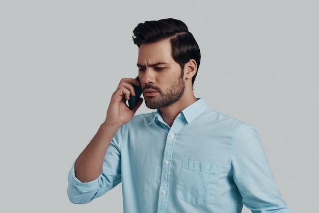 悪いニュース。灰色の背景に立ってスマートフォンで話している混乱した若い男