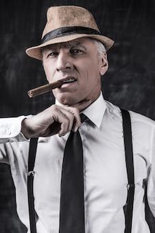 あなたにとって悪いニュース。帽子とサスペンダーで葉巻を吸って、暗い背景に立っている間彼の首に指を保持している偉そうな年配の男性
