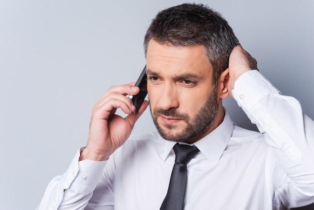나쁜 소식. 셔츠에 넥타이를 매고 전화 통화를 하고 회색 배경에 서 있는 동안 머리에 손을 잡고 있는 좌절된 성숙한 남자