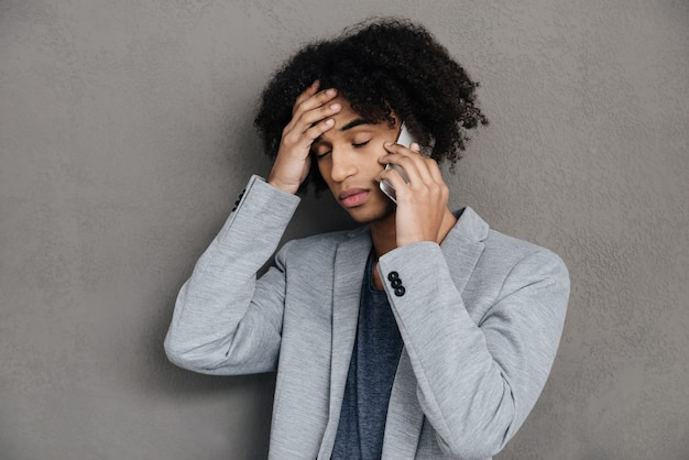 Bad news. frustrated young african man talking on mobile phone and holding hand in hair while standing against grey background