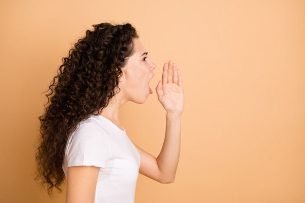 Bad news guys! profile photo of pretty lady yelling loud anger to empty space holding hand near mouth wear white casual outfit isolated beige pastel color background