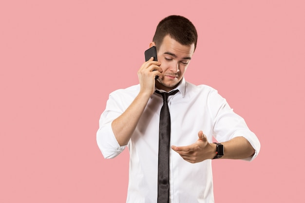 悪いニュース。携帯電話を持つハンサムなビジネスマン。ピンクに孤立して立っている若いビジネスマン