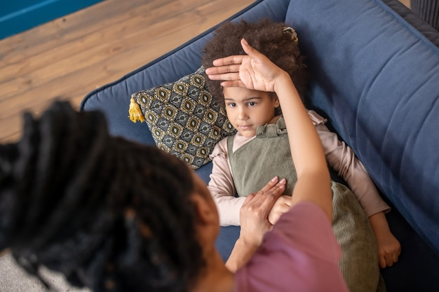 Bad news. mom touching forehead of sick little african american girl lying on pillow on sofa in room with her palm