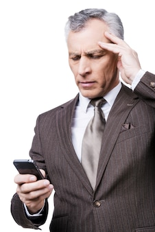 Bad news. portrait of frustrated mature man in formalwear holding the mobile phone while standing against white background
