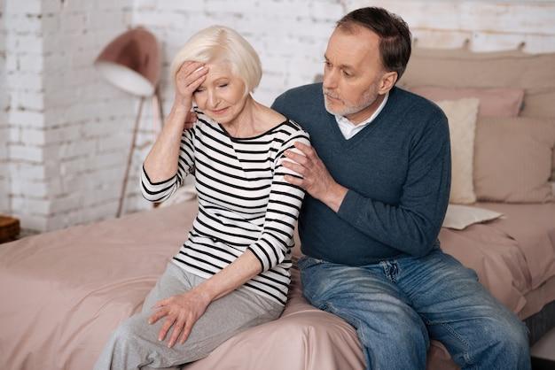 나쁜 소식. 수석 우울한 여자는 남편 근처의 침대에 앉아 손으로 이마를 만지고 있습니다.
