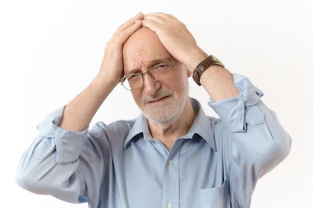 나쁜 소식, 스트레스 및 사람들 개념. 공식적인 옷과 그의 머리에 손을 잡고 안경에 좌절 된 60 세 백인 남자의 스튜디오 샷, 문제 때문에 슬픈 표정을 강조하는 데