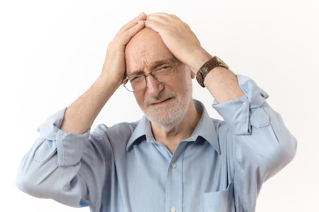 Bad news, stress and people concept. studio shot of frustrated sixty year old caucasian man in formal clothes and eyewear holding hand on his head, having stressed mournful look because of problems