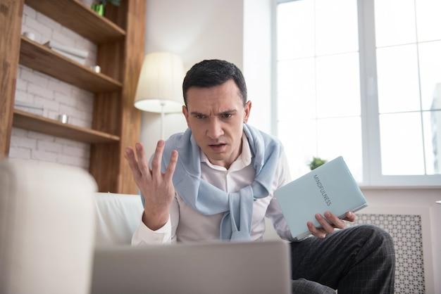 悪いニュース。ノートパソコンを使用しながら本を持っている不満の怒っている男