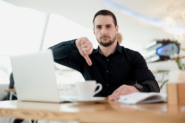 Bad news! unsatisfied attractive male freelancer showing thumb down, looking at camera with sad face. cozy coffee shop on background. man in black shirt tired. laptop and cup of flat white on table.