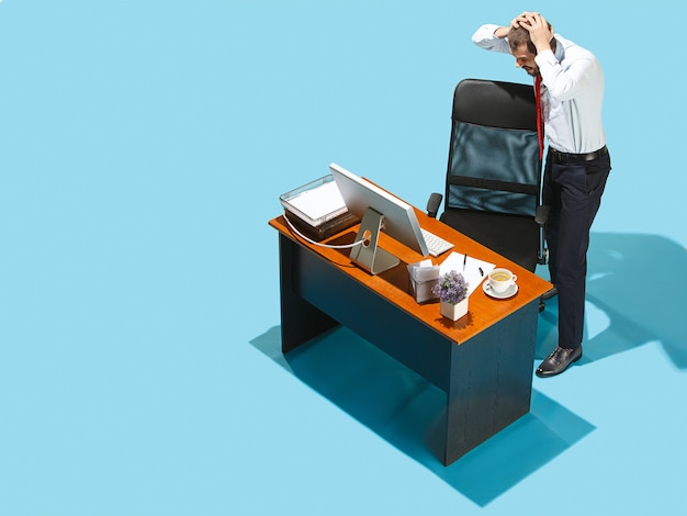 Bad news. above view of businessman working on laptop. young distressed frustrated man standing at office table. business, workplace concept. human emotions, facial expressions concepts. blue studio