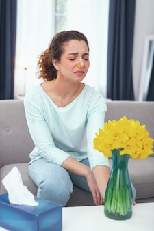 Плохой подарок. юная красивая женщина с заткнутым носом страдает от последствий подаренного ей ароматного цветочного букета
