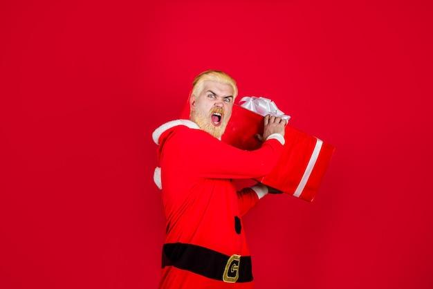 Bad santa. angry santa with present. new year gift. christmas decorations. santa claus gifting present. present box.