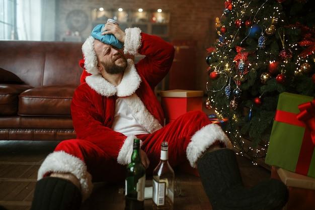 ソファに座っているアルコールのボトルと悪いサンタクロース