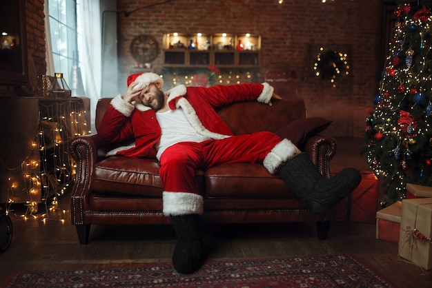 Bad santa claus with hangover sitting on couch