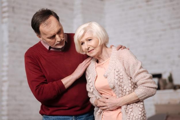 悪い寿司。夫が彼女を支えている間、腹痛のために彼女のタミーに寄りかかって触れている年配の女性。