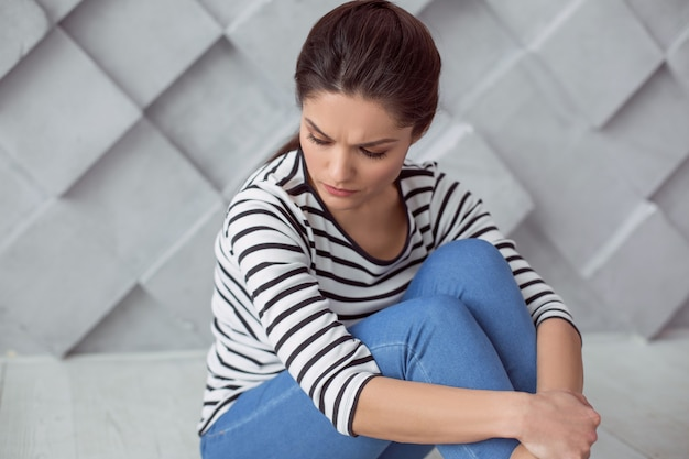 Bad thoughts. depressed cheerless young woman sitting on the floor and thinking about her life while being in a bad mood