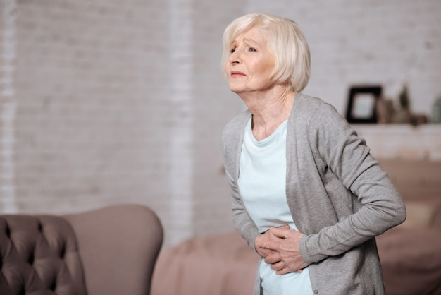 Bad toxication. side view of pretty elderly lady leaning and touching her stomach because of stomachache.