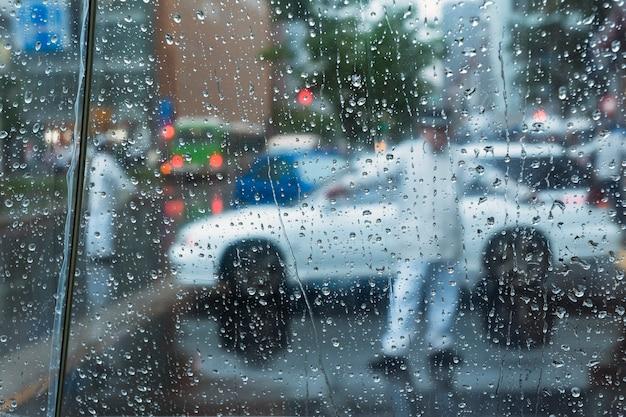 東京の街並みから撮影された悪天候の街。透明な傘のプラスチックの上を流れる雨滴に焦点を当てる