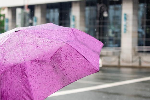 悪天候。雨の日。都市の背景に雨粒の傘。シティストリートスタイル。