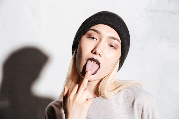Bad woman in black hat showing tongue and middle finger