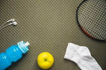 Badminton; apple; sock; water bottle and earphone on textured pattern background