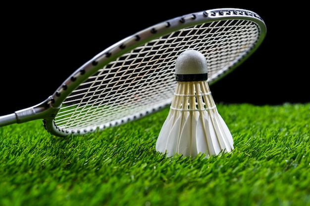 Badminton ball and racquet on grass in black background