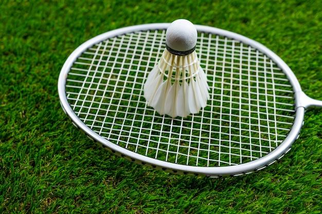 Badminton ball and racquet on grass
