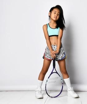Модель preteen девушки бадминтона азиатская представляя с портретом полной длины ракетки изолированным на белизне. молодой игрок в бадминтон или теннис. модная спортивная одежда, спорт и активное детство, здоровый образ жизни