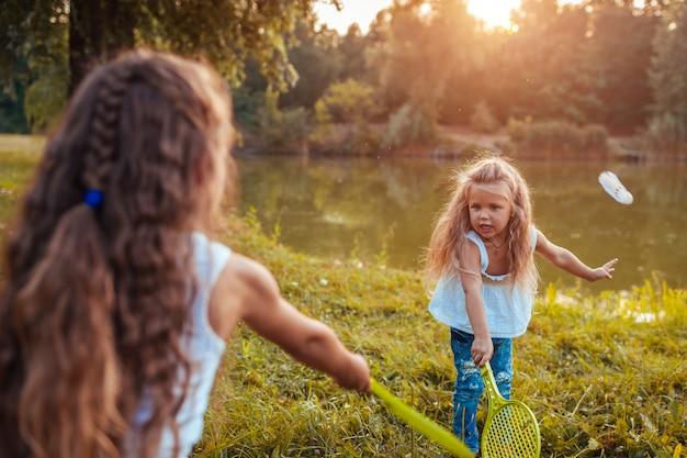バドミントン。春の公園で妹とバドミントンをしている女の子。屋外楽しんでいる子供。