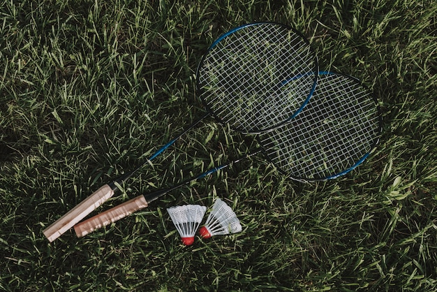 Badminton racket and shuttlecock on grass.