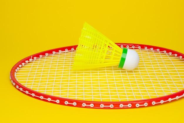 Бадминтонный волан и ракетка, изолированные на желтом